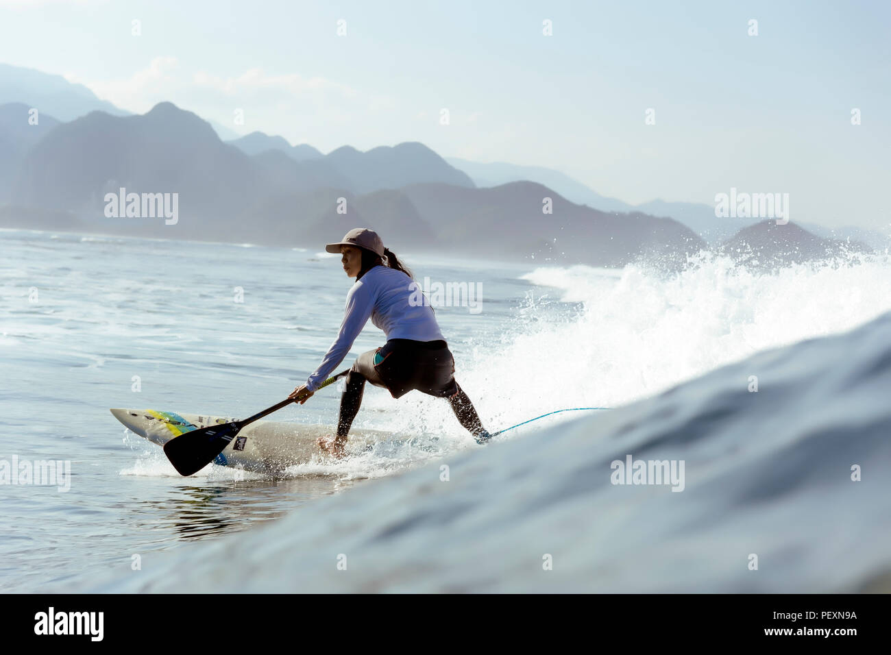 Donna paddle surf in mare Foto Stock