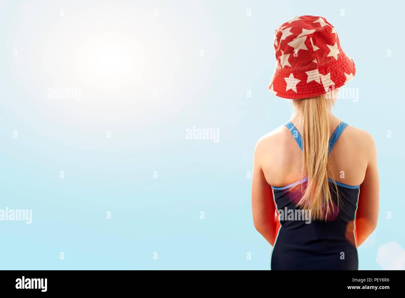 Ragazza di indossare il costume da bagno e cappello, vista posteriore. Immagini Stock