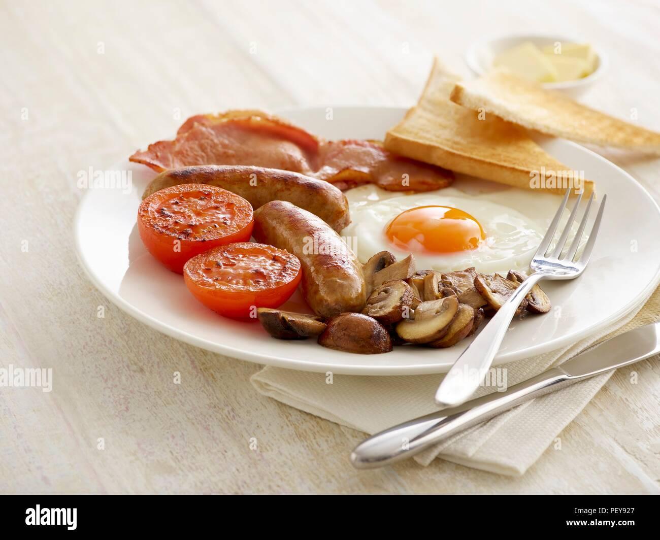 La completa prima colazione inglese è servita su una piastra. Immagini Stock