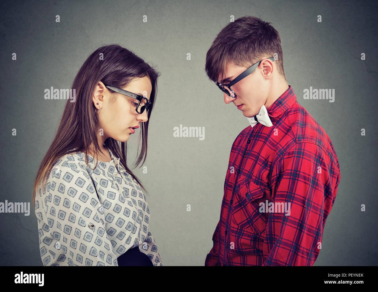 Vista laterale del giovane uomo e donna che guarda verso il basso che si trova di fronte a sentimenti di tristezza e dolore Immagini Stock