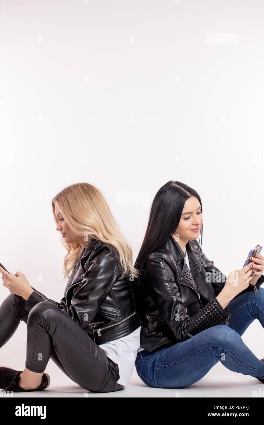 Due donne bellissime ignorando ogni altra, navigando in rete. Tempo libero , hobby Immagini Stock
