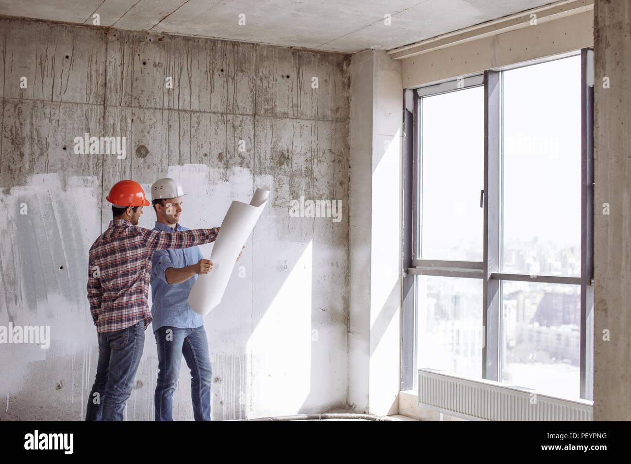 14041678aa Impresa edile. bello ingegnere è che mostra la costruzione di un piano per  il cliente