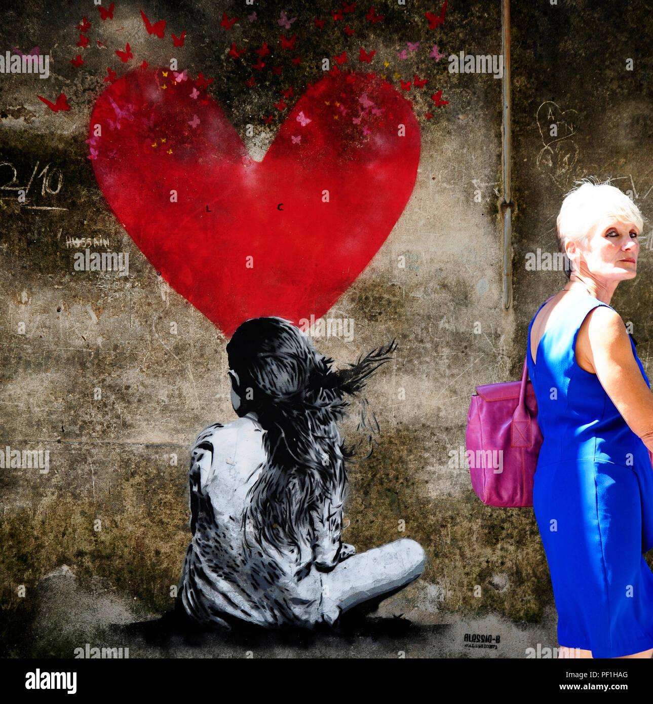 Arquà Petrarca, PD, Italia - 15 agosto 2018, dipinta su un muro in Arquà Petrarca. Una bambina visto da dietro e un grande cuore in background. Un Foto Stock