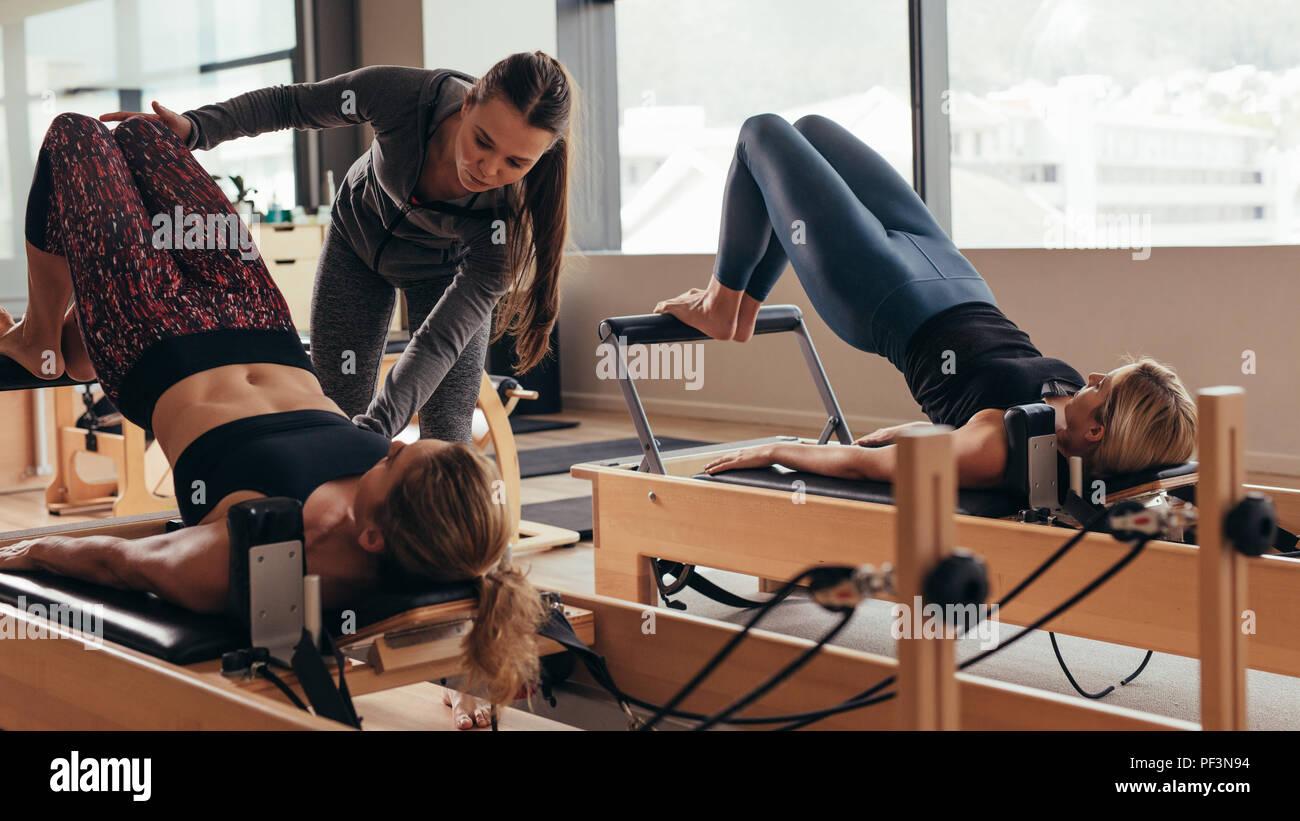 Pilates Formazione Istruttori donne presso la palestra. Due donne fitness facendo pilates allenamento sulla attrezzature pilates. Foto Stock