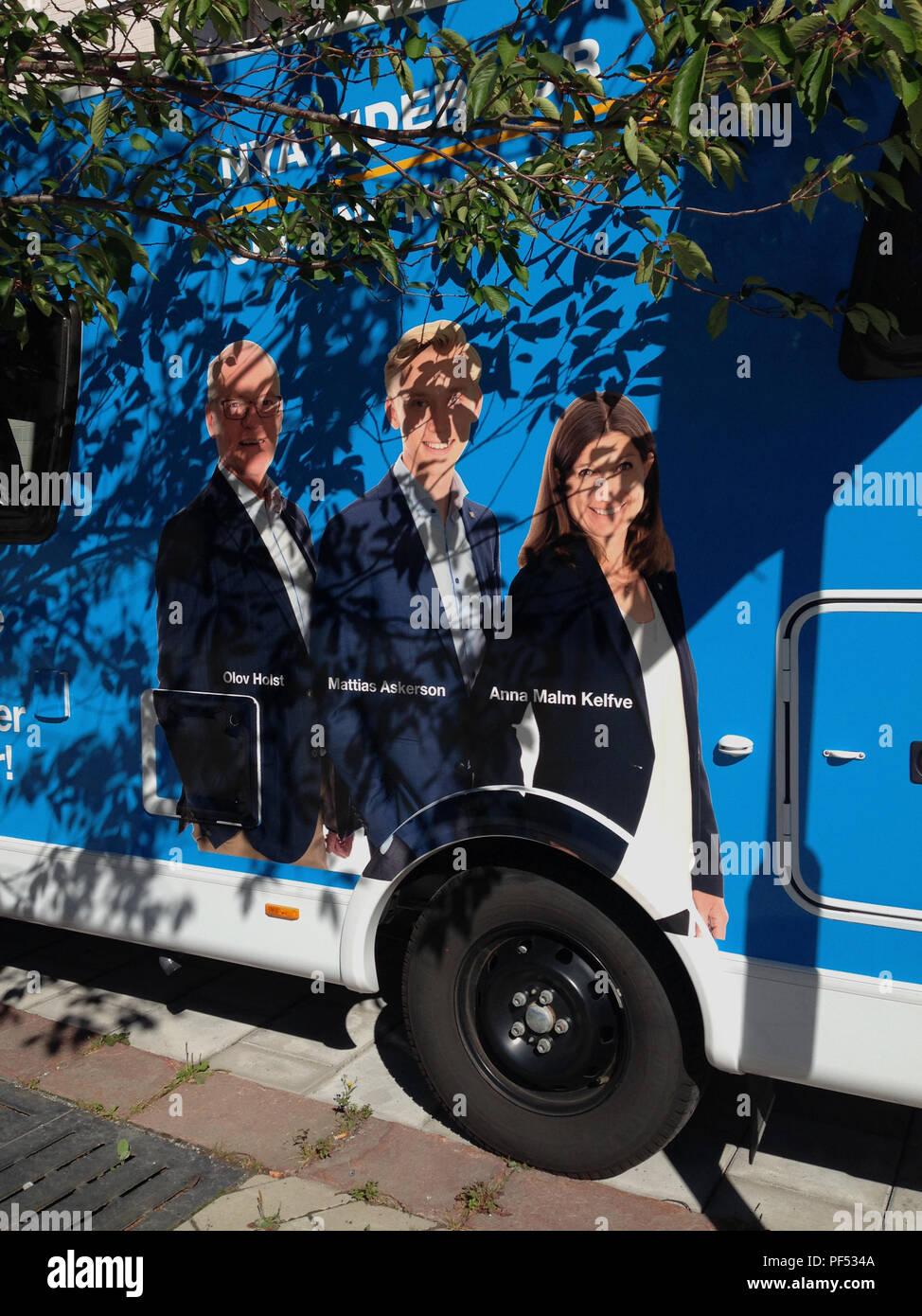 Pre-campagna elettorale con ritratti del partito moderato svedese (M - Modernaterna) candidati, su un veicolo parcheggiato a fianco di un albero, colata le sue foglie ombre su grafica. Märsta, Sigtuna kommun, Stoccolma, Svezia. Immagini Stock