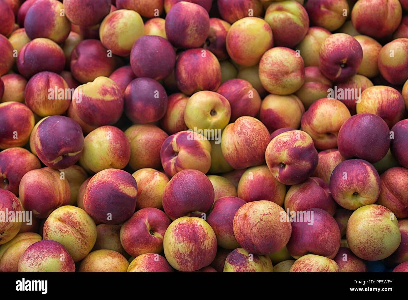 Nettarine (Prunus persica var. nectarina), buccia liscia di pesche, pila nel mercato, beckground Immagini Stock