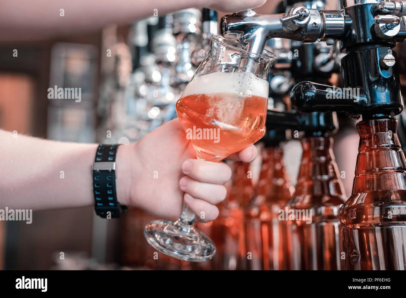 Barman tenendo il vetro durante il riempimento con il mestiere di birra scura Immagini Stock