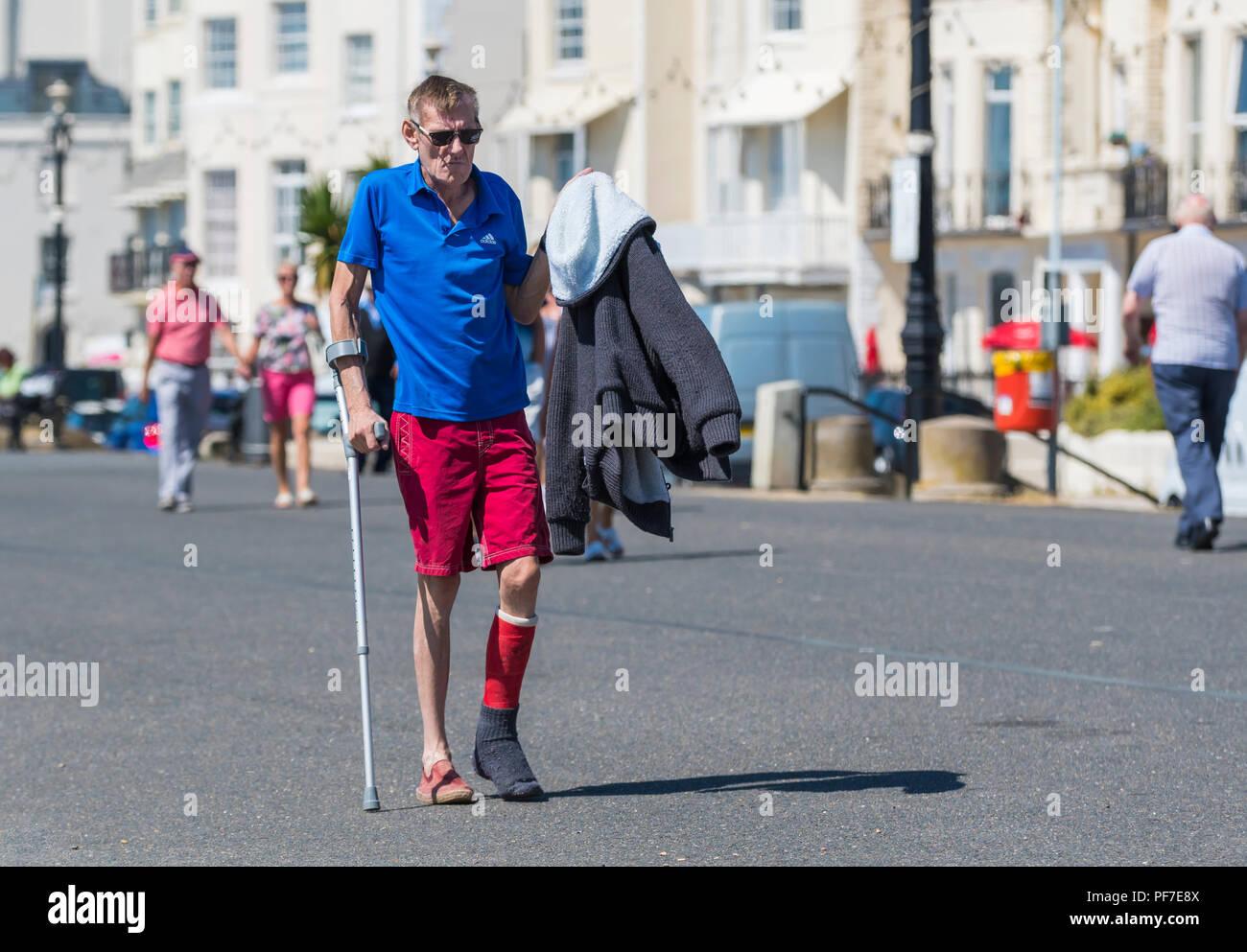 Uomo con gamba ferita camminare con l'aiuto di una stampella. Uomo che cammina con le stampelle. Immagini Stock