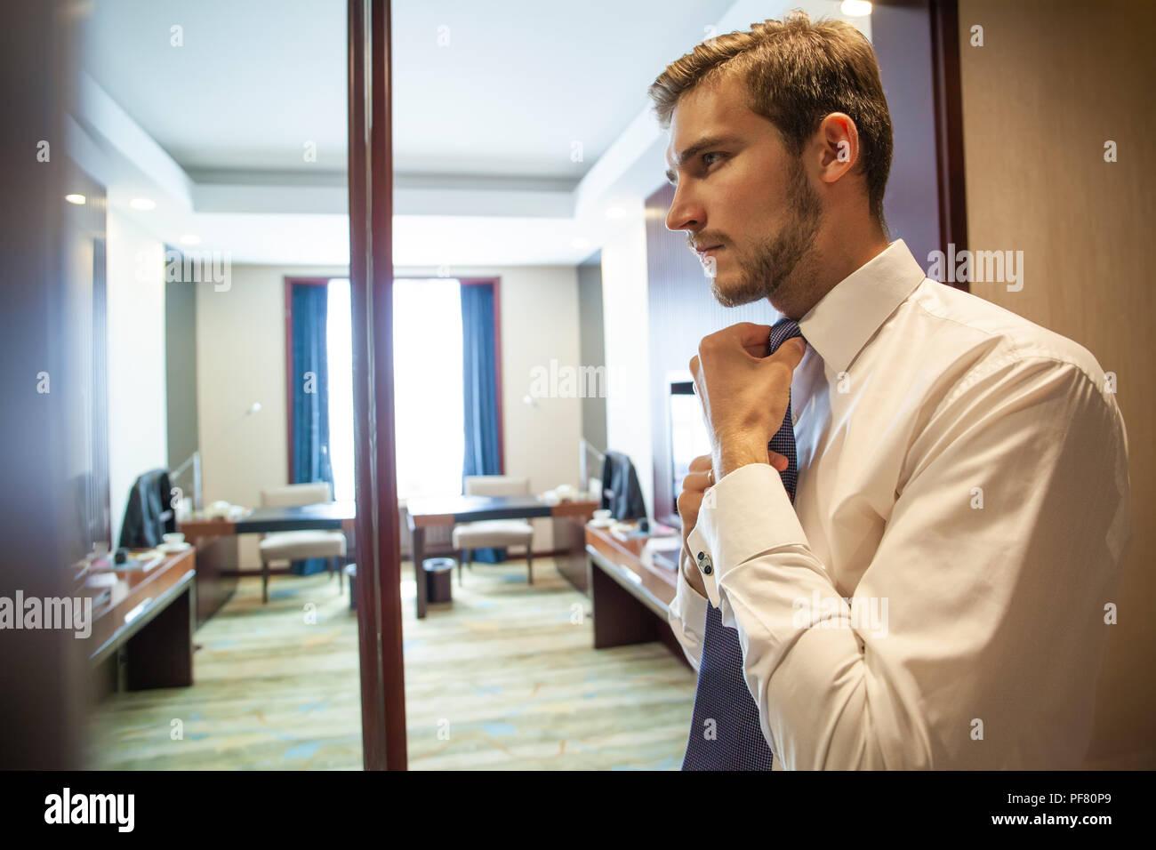 Persone, Business,moda e abbigliamento concetto - close up Uomo in camicia vestirsi e regolazione del tirante sul collo a casa. Immagini Stock