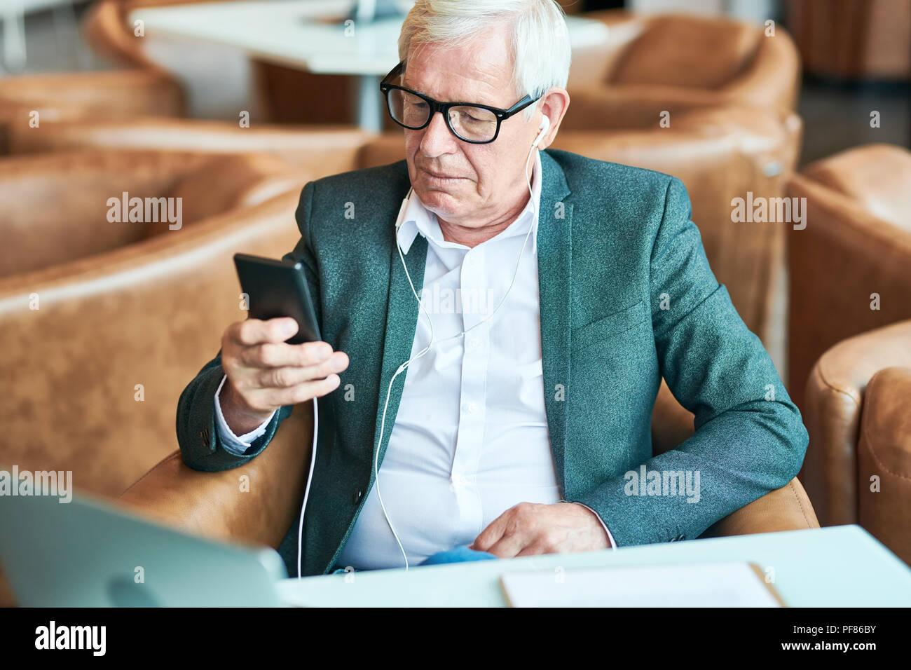 Senior contemporaneo uomo utilizza lo smartphone in Cafe Immagini Stock