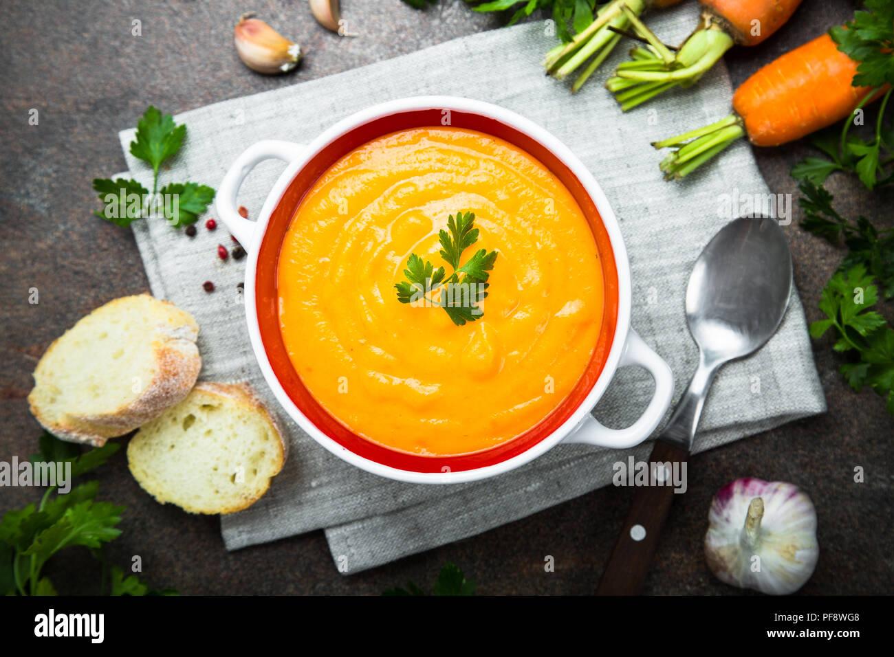 La carota Crema di zucca-zuppa su pietra scura tabella. Vegetariano zuppa di verdure. Vista dall'alto. Foto Stock