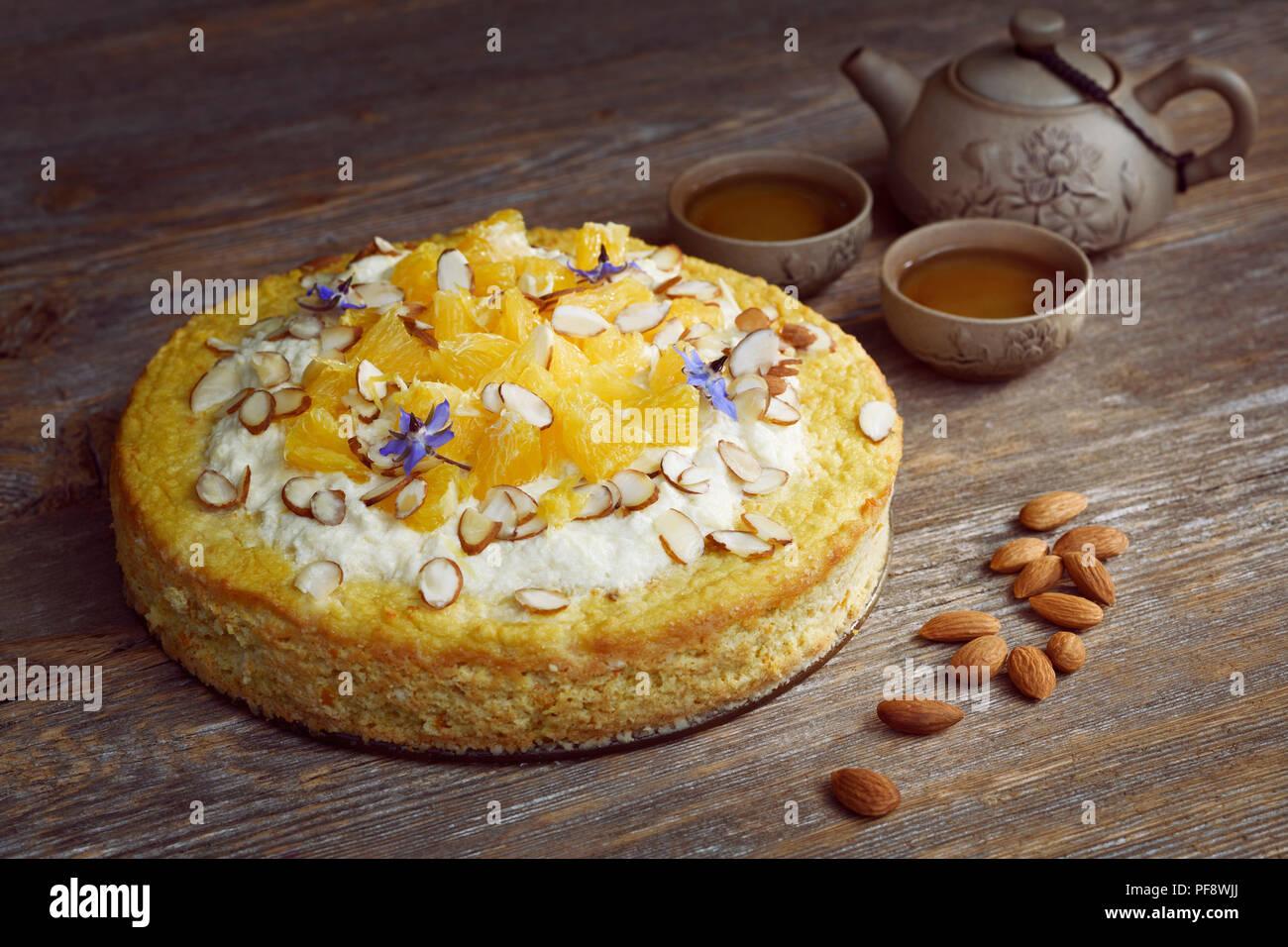 Una sana fatta in casa flourless, senza zucchero, dairy-free vegan torta a base di farina di mandorle, arance e noci di cocco, cibo artistico ancora in vita con una teiera di argilla Immagini Stock