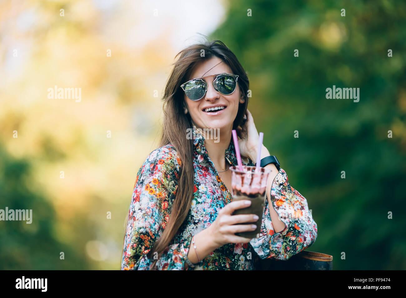 Giovane donna in occhiali da sole con il frullato. Outdoor Lifestyle autunno ritratto di bella donna sorridente. Immagini Stock