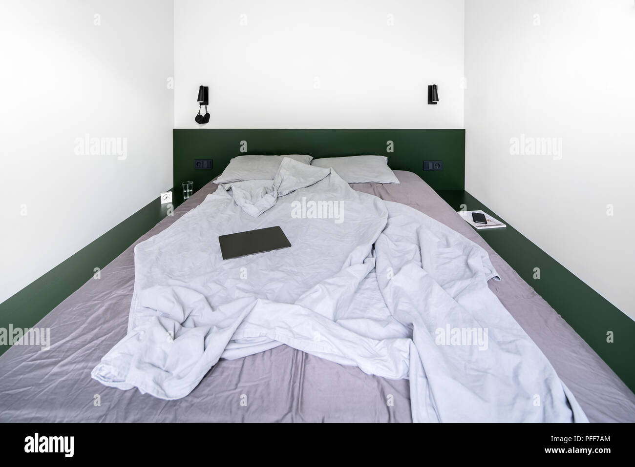 Camera da letto in stile moderno con pareti bianche. vi è un verde