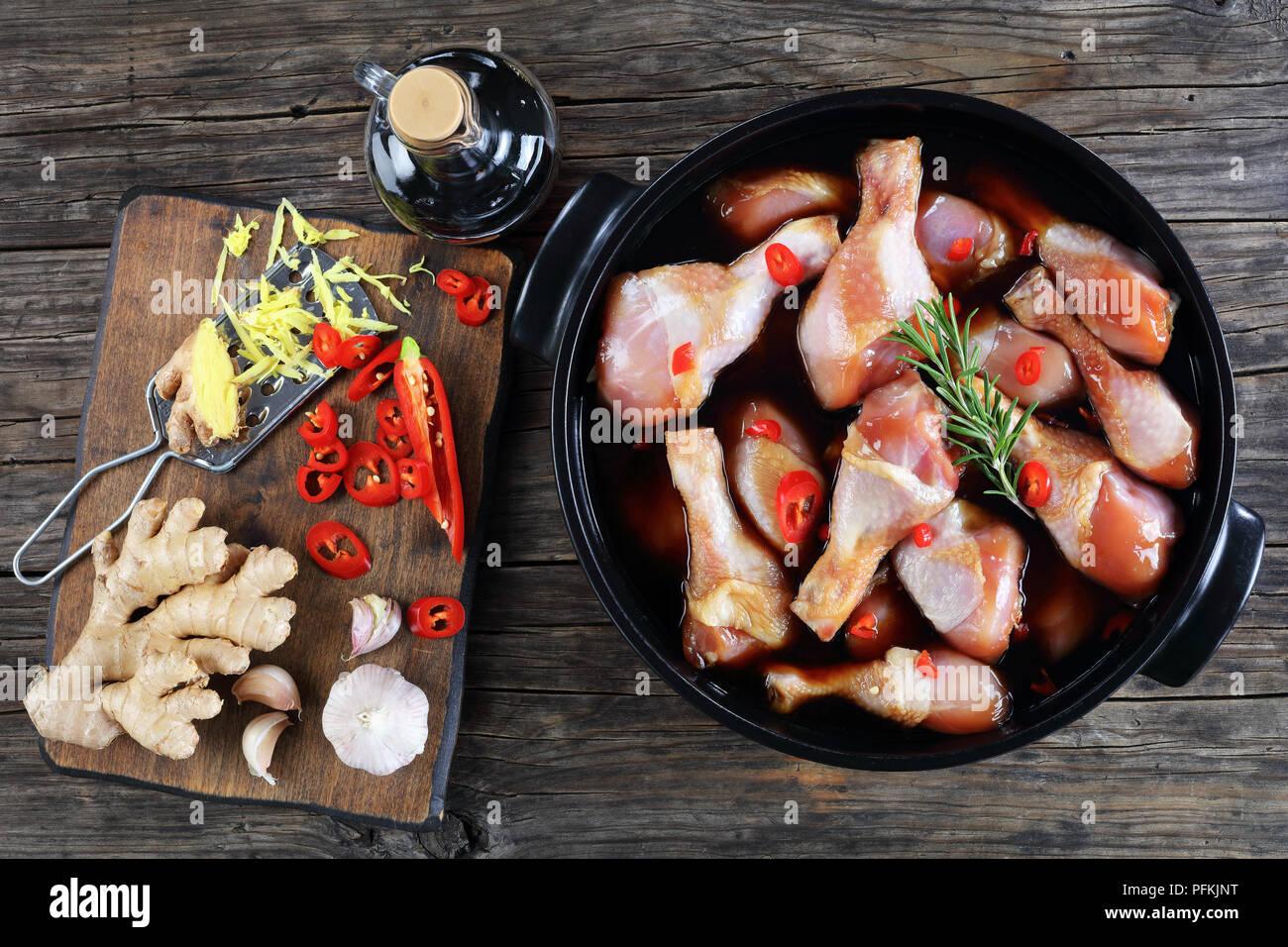 Il pollo crudo marinato bacchette con fatti in casa piccante salsa teriyaki in pot nero. ingredienti sul tagliere di legno sul tavolo di legno, vista orizzontale Immagini Stock