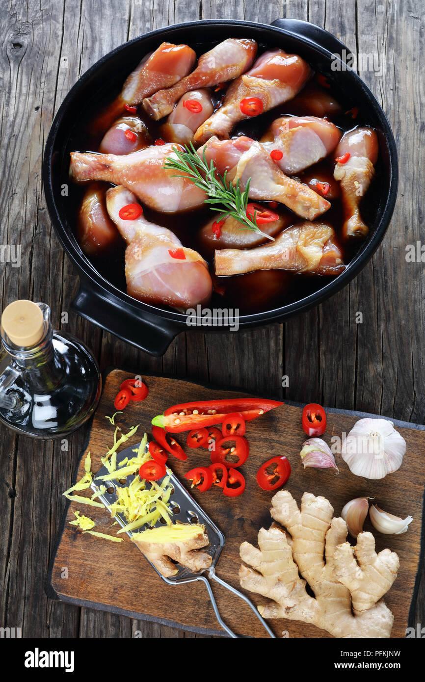 Il pollo crudo marinato bacchette con fatti in casa piccante salsa teriyaki in nero piatto. ingredienti sul tagliere di legno sul tavolo di legno, vista verticale Immagini Stock