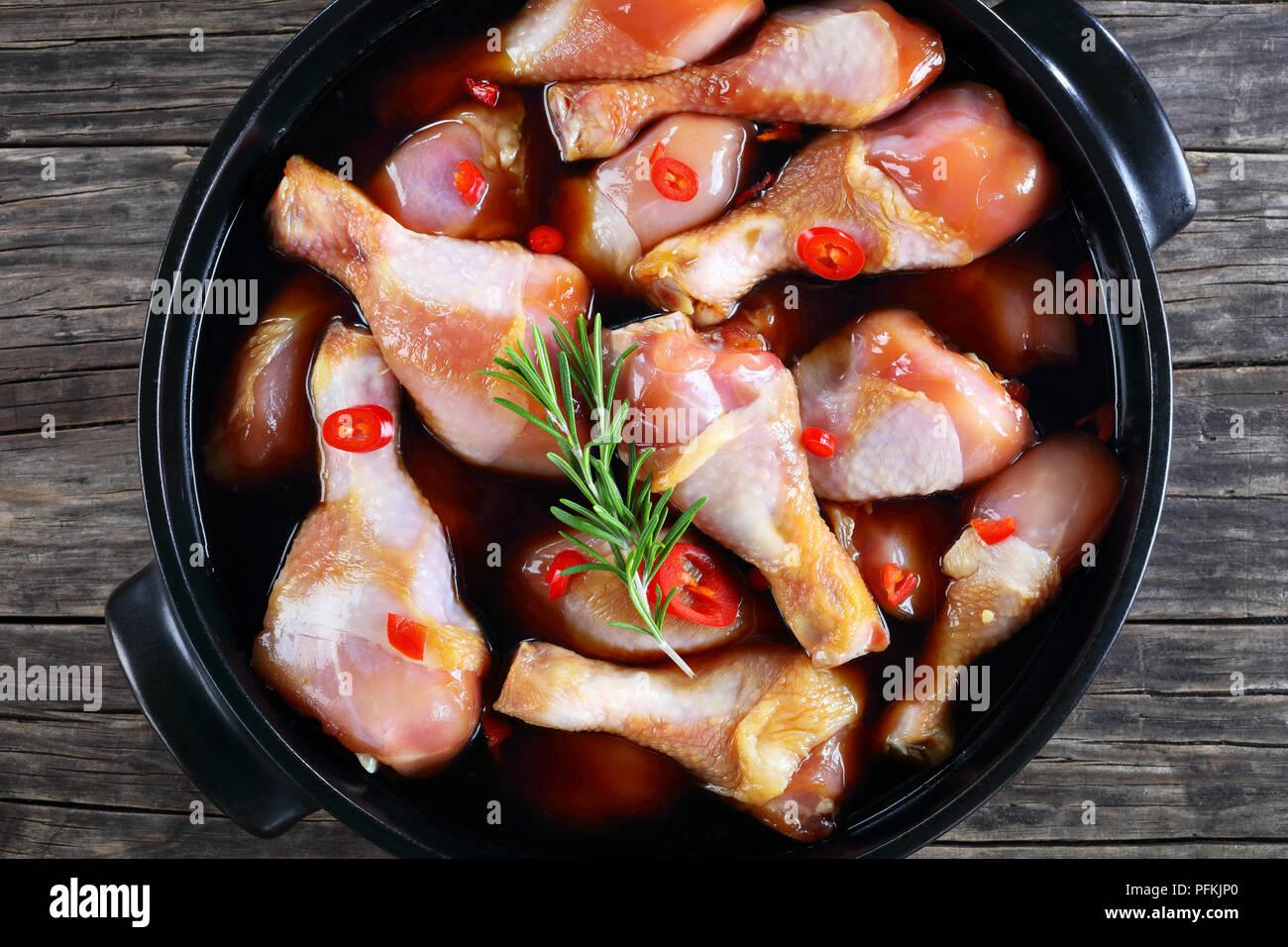 Il pollo crudo marinato bacchette con fatti in casa piccante salsa teriyaki in pot nero., vista da sopra, close-up Immagini Stock