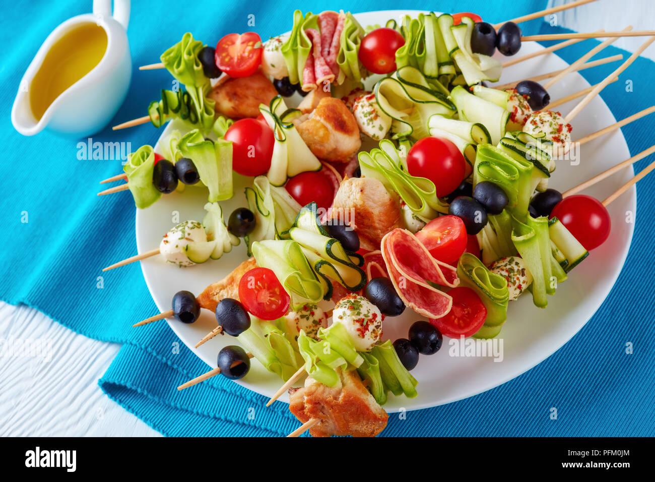 Carne di pollo shish kebab spiedini con nastri di zucchine, pomodori, mozzarella, sfere, fette di salame, olive nere su una piastra bianca, vista orizzontale da Immagini Stock