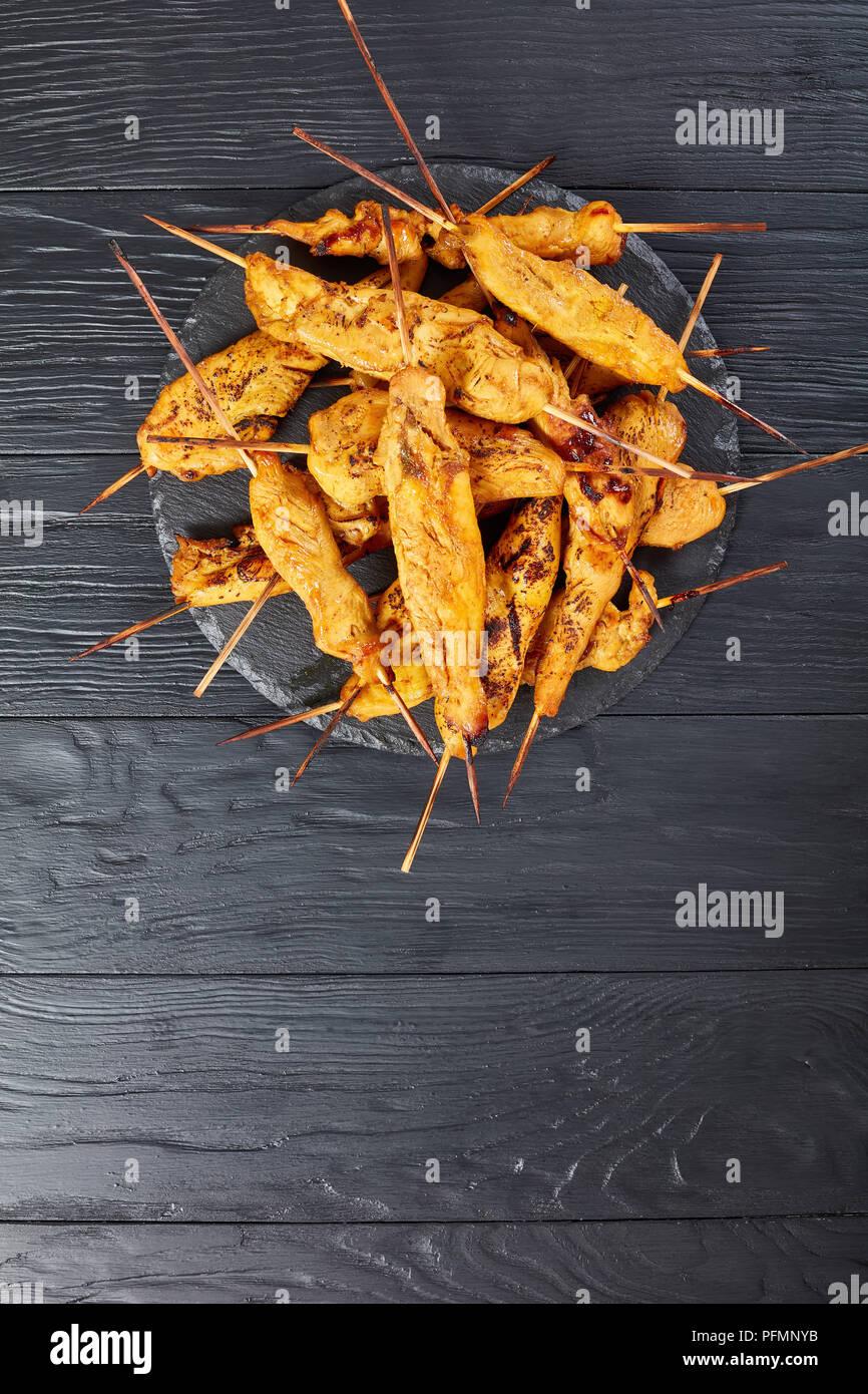 Pollo satay su spiedini su una pietra nera il vassoio su un tavolo di legno, verticale vista da sopra Immagini Stock