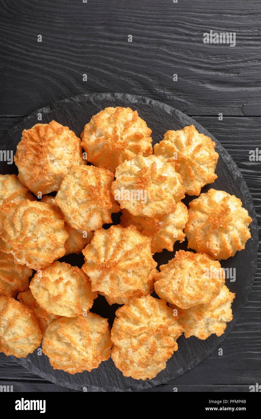 Deliziosi biscotti di cocco su una piastra su un tavoli in legno nero, verticale vista da sopra Immagini Stock