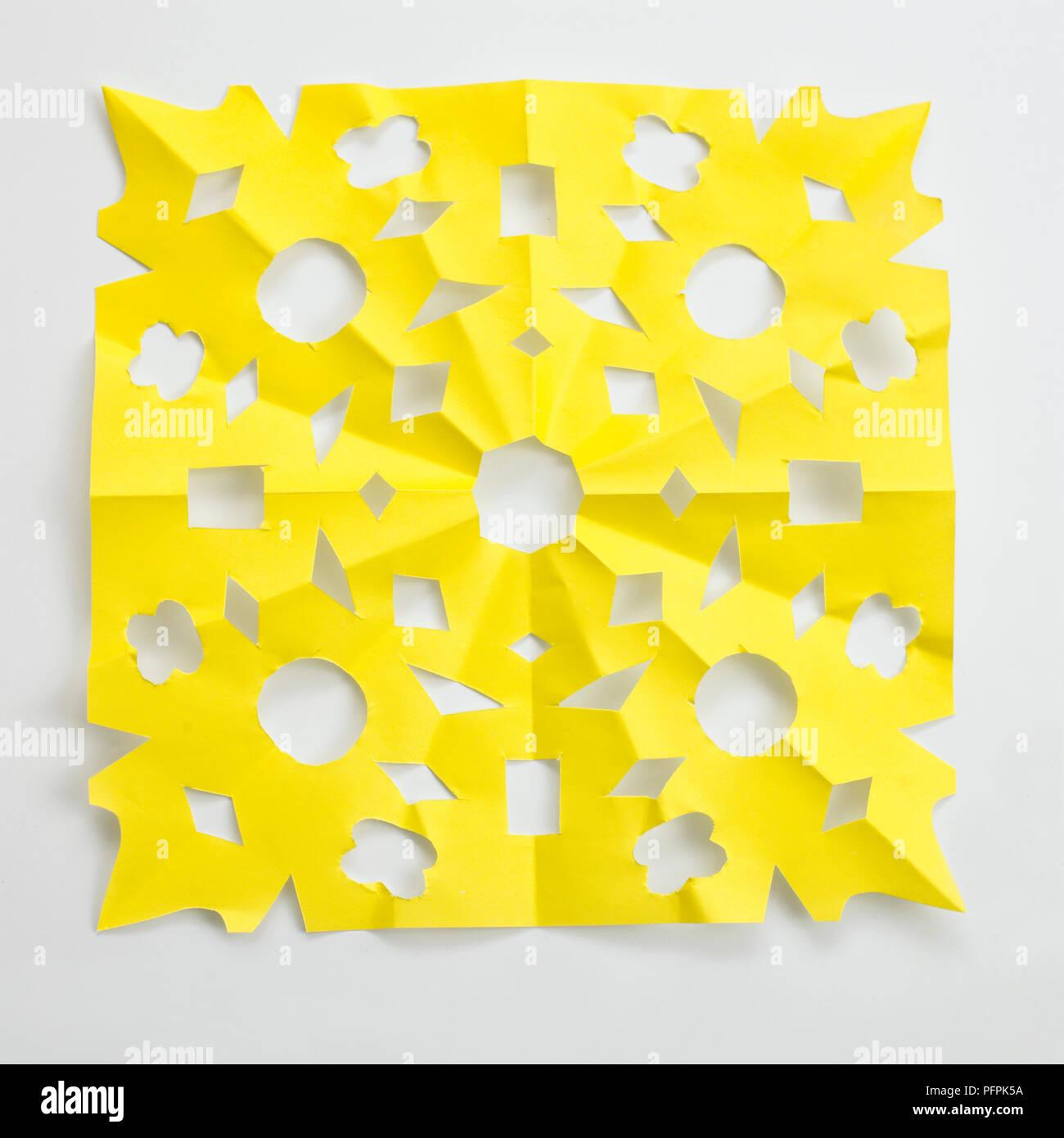 Foglio di carta gialla con schema simmetrico tagliati in essa Immagini Stock