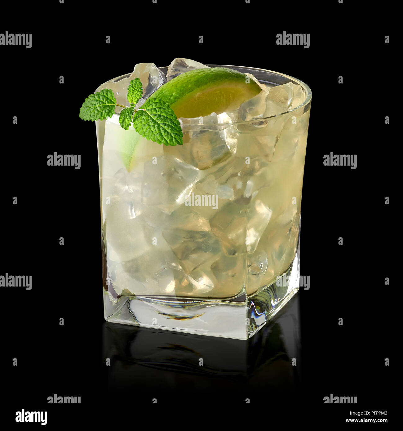 La vodka lime, caipirinha, succhiello o gin tonic con il ghiaccio in vetro su sfondo nero Immagini Stock