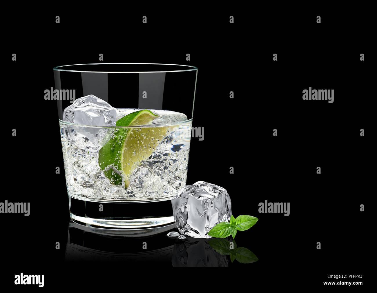 Il gin tonic o vodka lime e foglie di basilico isolati su sfondo nero Immagini Stock