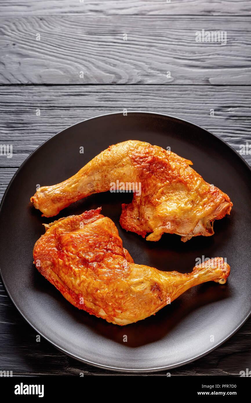 Pollo fritto con gambe dorate e croccanti pelle su una piastra nera su una tavola di legno, vista verticale dal di sopra, close-up Immagini Stock