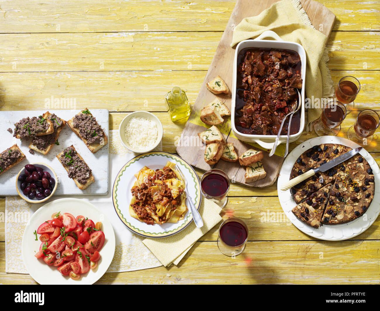 Autunno Toscano cena, compresi i crostini di fegatini di pollo (fegato), pappardelle al ragu, spezzatino di manzo (stufato di manzo), il castagnaccio Torta di castagne Immagini Stock