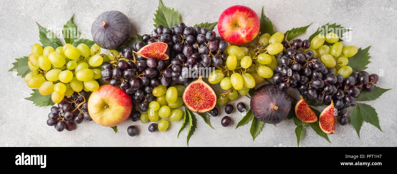 Banner Di Freschi Frutti D Autunno Uva Nera E Verde Fichi E Foglie Su Un Tavolo Grigio Foto Stock Alamy