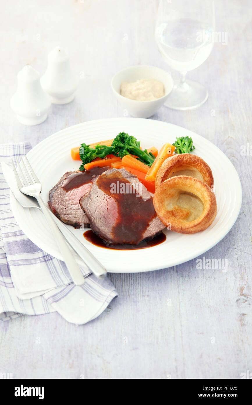 Arrosto Domenicale, arrosto di manzo con sugo di carne, verdure e Yorkshire pudding Immagini Stock