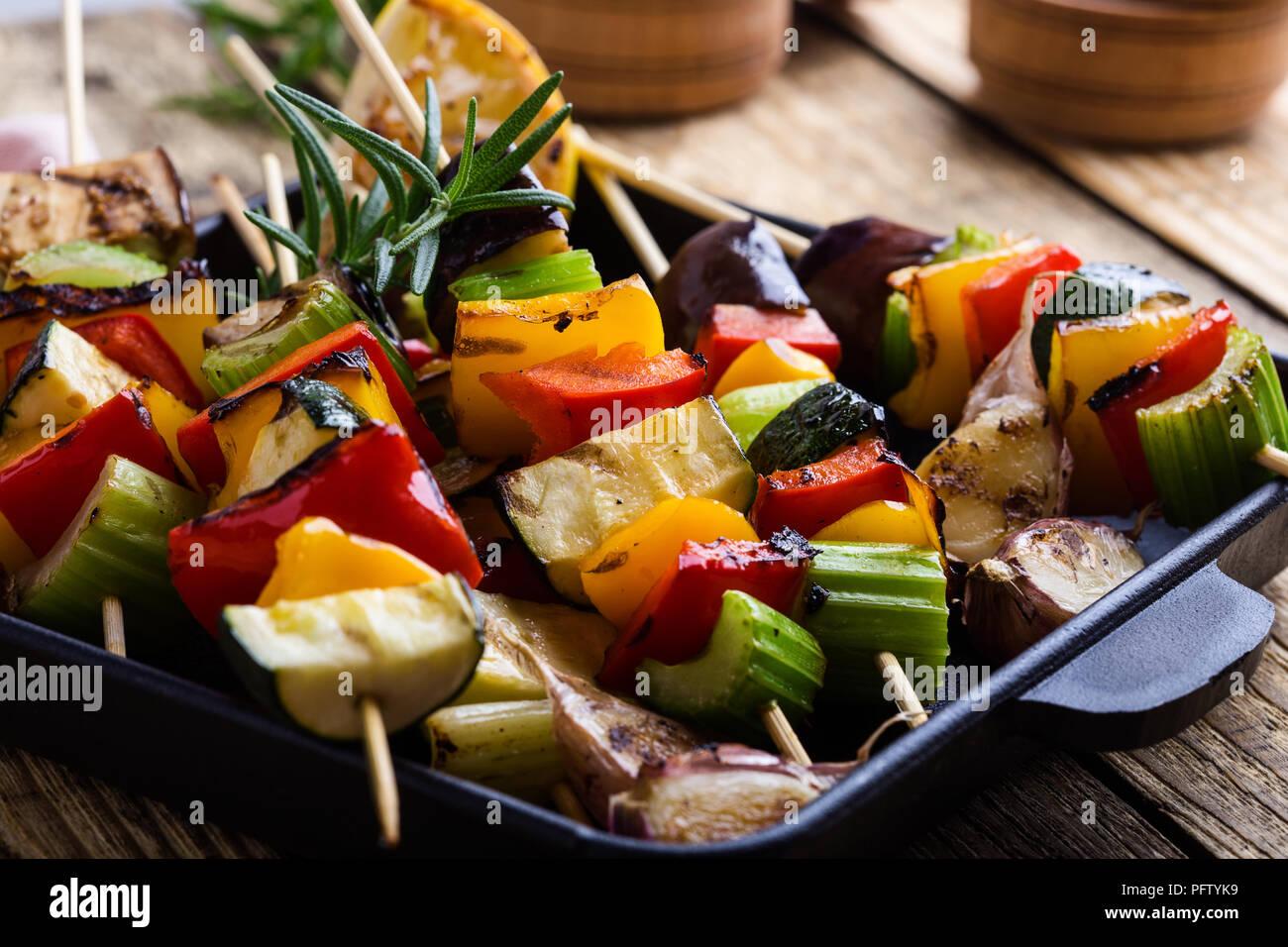 Grigliata di verdure colorate spiedini sulla padella in ghisa. Vegano pasto estivo su tavola in legno rustico Immagini Stock