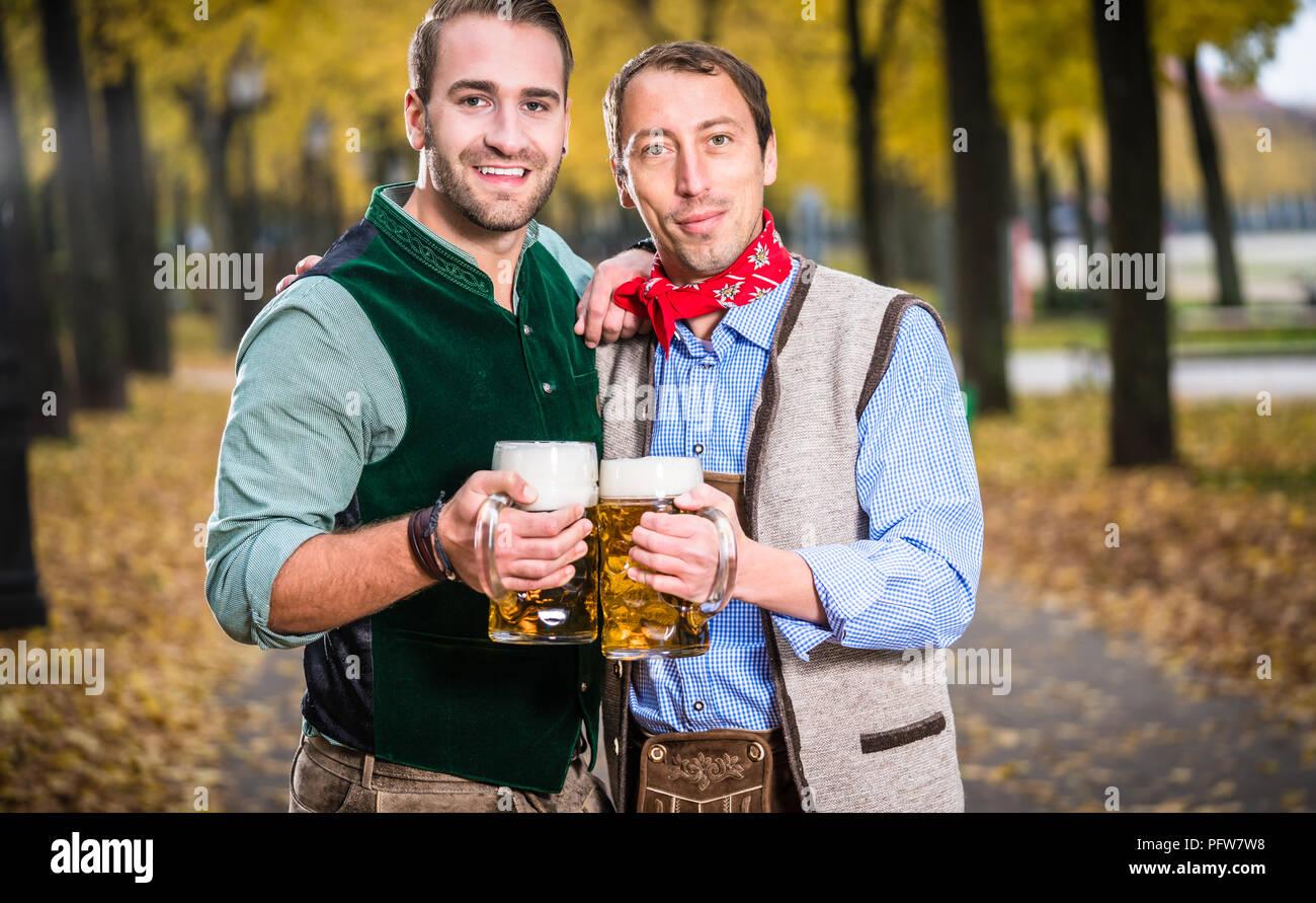 Gli uomini in bayrischer Tracht tintinnanti bicchieri di birra Immagini Stock