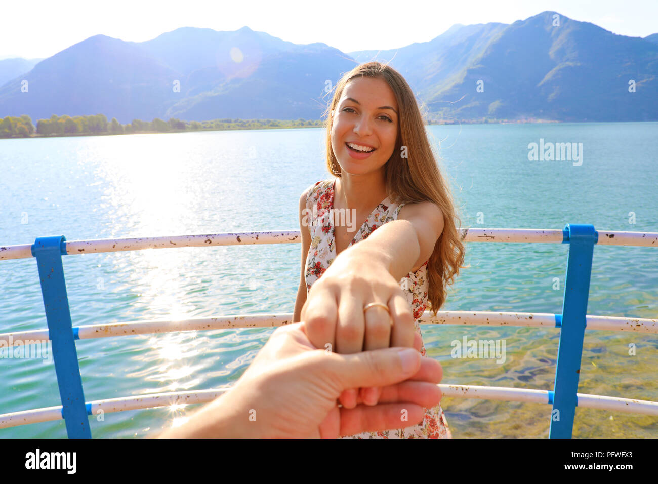 Ritratto di felice giovane donna che mostra il suo anello di nozze con maschio mano azienda con il suo bellissimo paesaggio naturale sullo sfondo, per concentrarsi sulla donna Immagini Stock