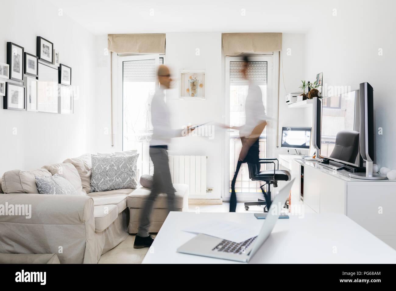 Due uomini occupati in movimento nella home office Immagini Stock