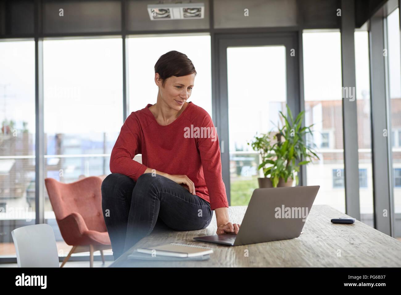 Donna sorridente seduto sulla tavola di casa utilizzando laptop Immagini Stock