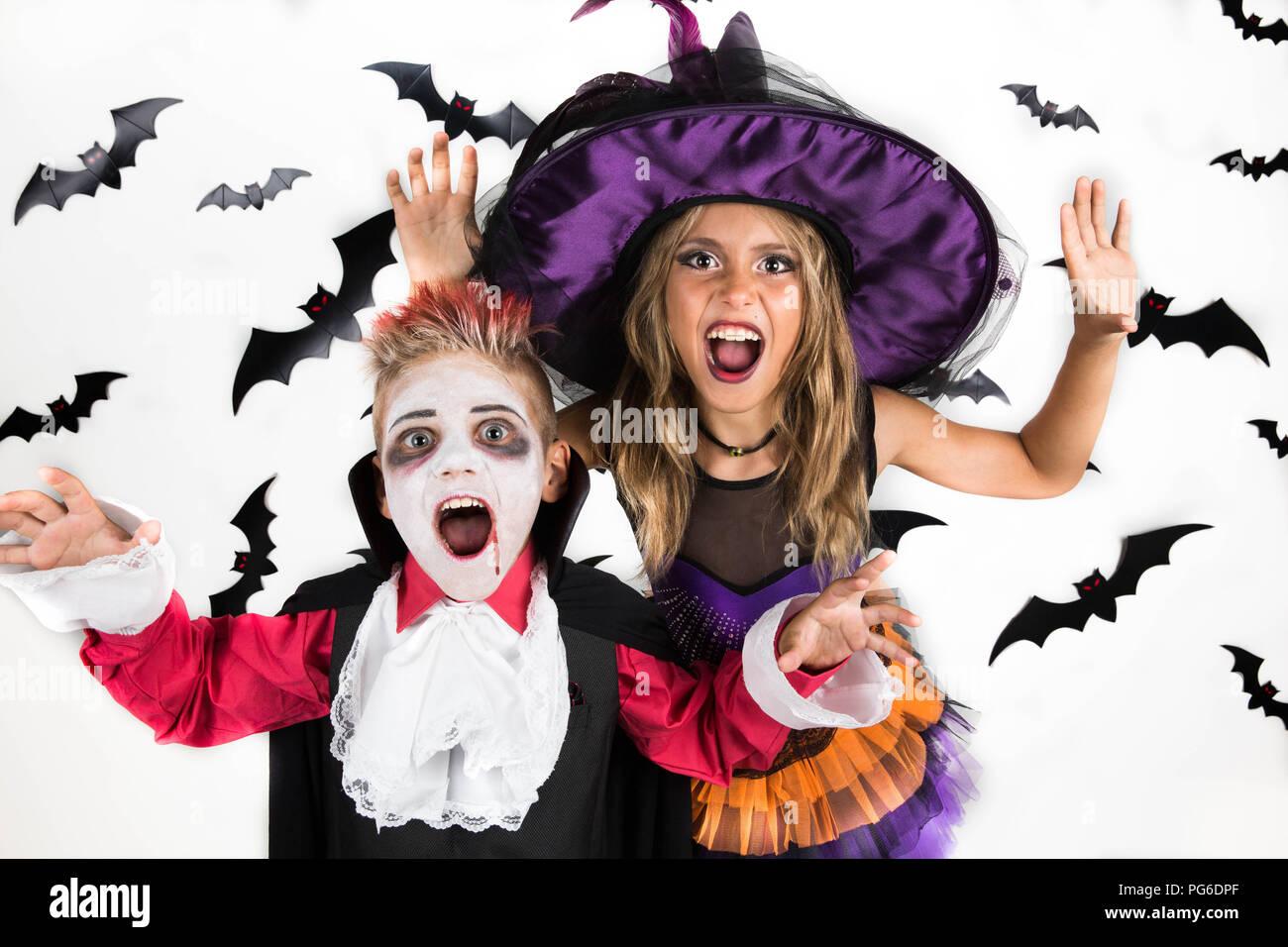 Dolcetto o scherzetto? Kids spaventare le persone nella notte di Halloween per guadagnare caramelle secondo la tradizione della vacanza Immagini Stock