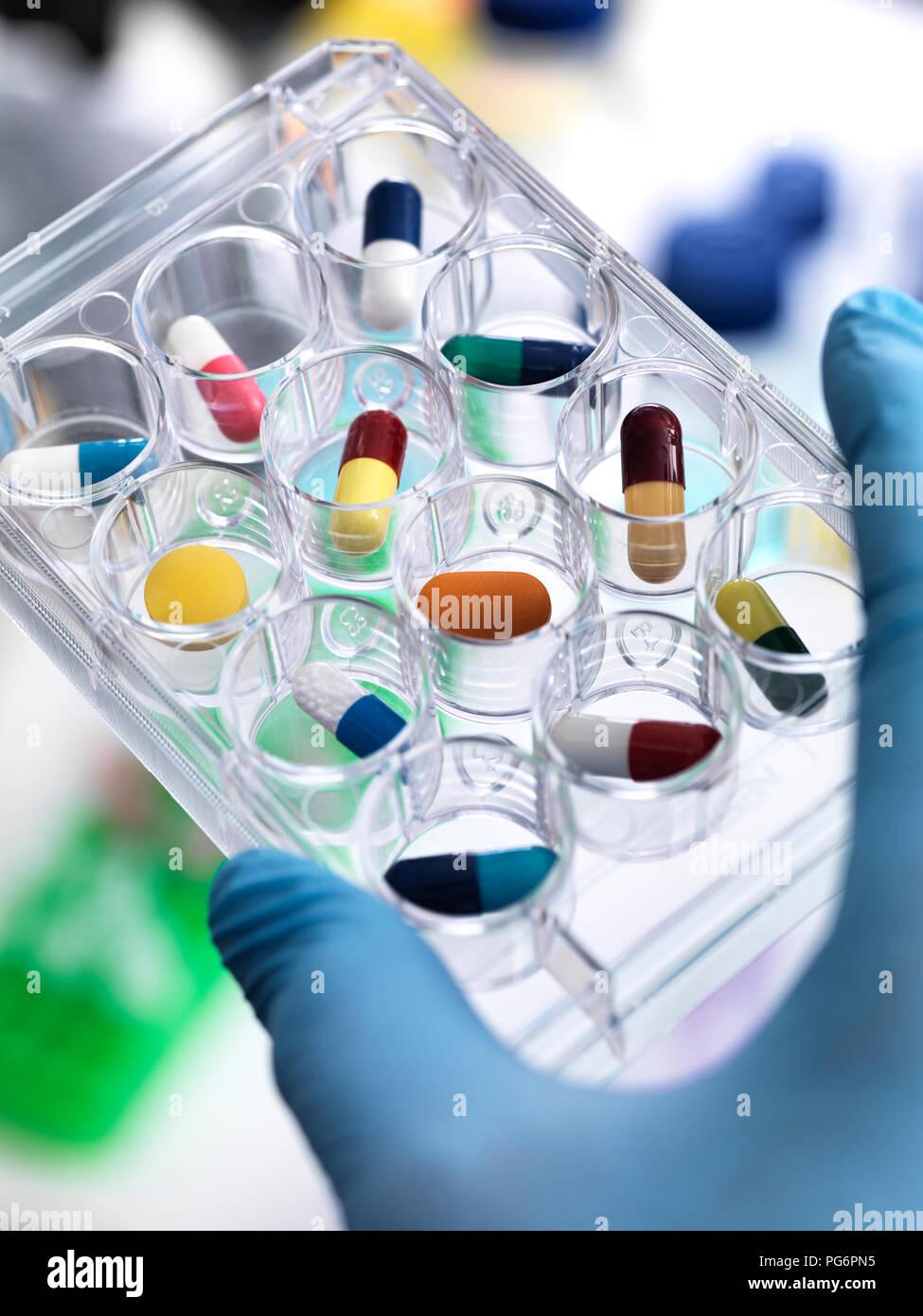 La ricerca farmaceutica, scienziato tenendo un multi pozzetti contenenti farmaci per essere testato in laboratorio Immagini Stock