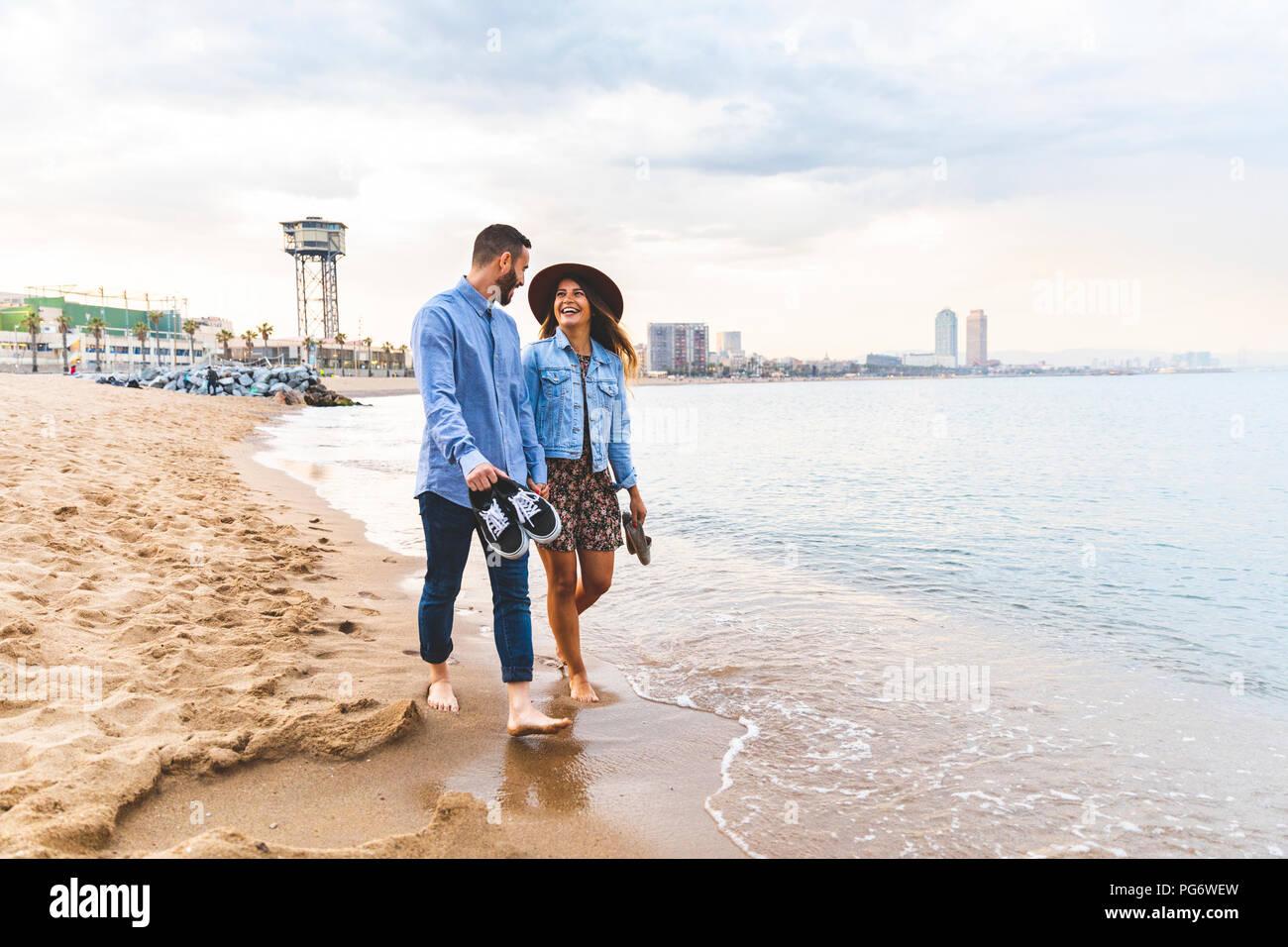 Spagna, Barcellona, giovane correre a piedi nudi sulla spiaggia Immagini Stock