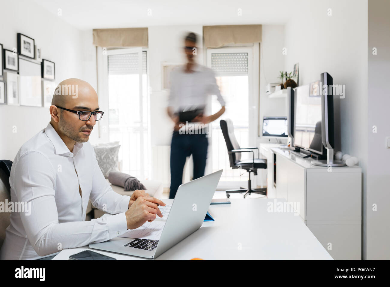 Uomo con notebook in ufficio a casa con il collega passato in movimento Immagini Stock