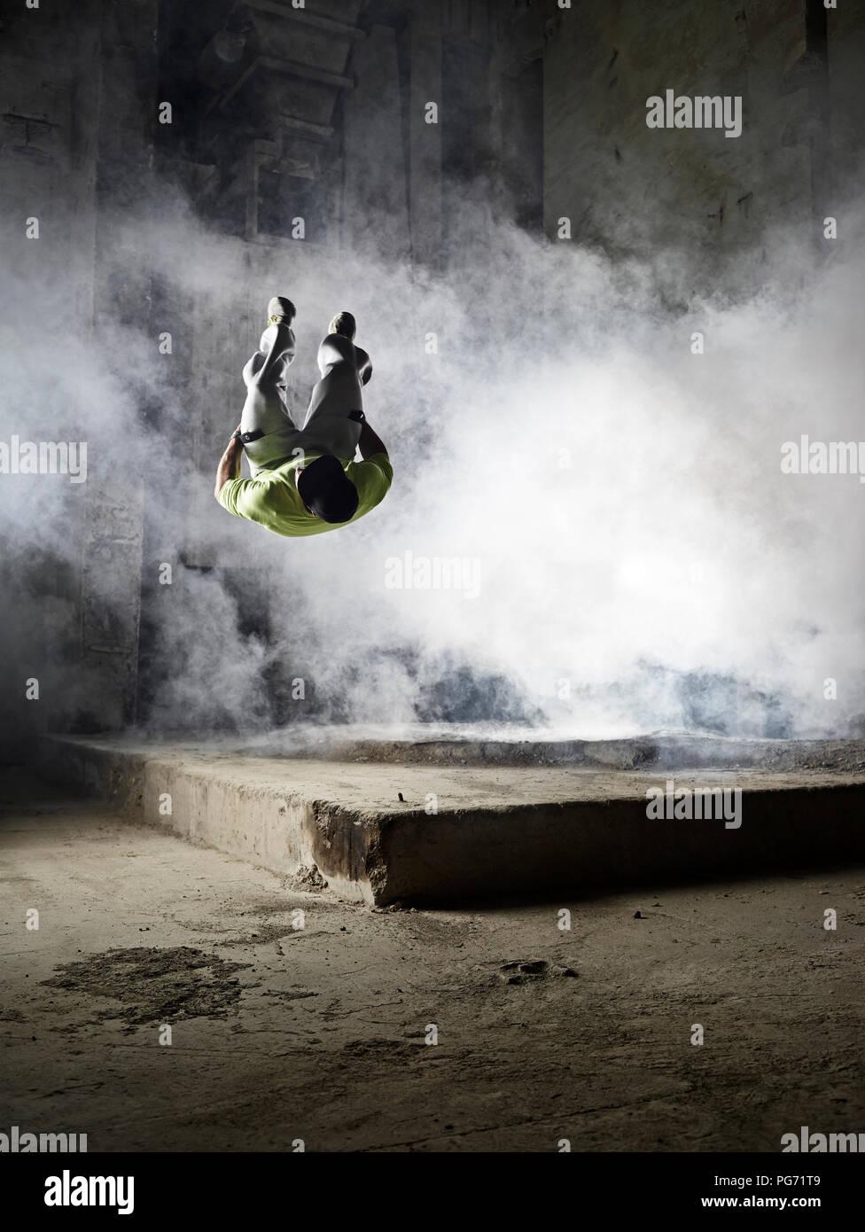 Uomo di saltare in una nube di polvere durante l'esercizio freerunning Foto Stock