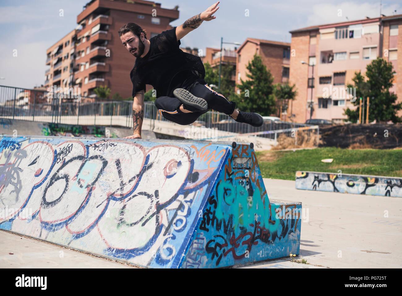 Tatuato uomo che fa parkour in uno skatepark Immagini Stock