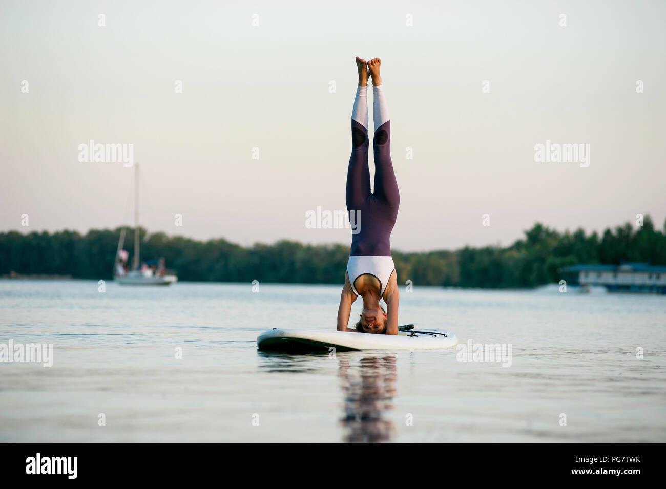 Stand Up Paddle board yoga eseguita da ragazza bella sulla città luminosa sullo sfondo, ragazza è in piedi sulla sua testa Immagini Stock