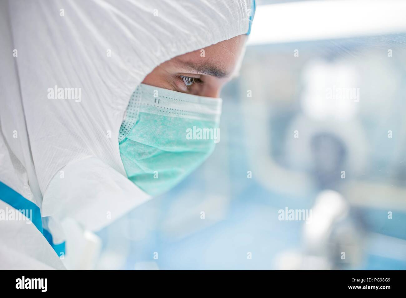 Close-up di un tecnico di laboratorio che indossa una tuta protettiva e maschera per il viso in un laboratorio che deve mantenere un ambiente sterile. Foto Stock