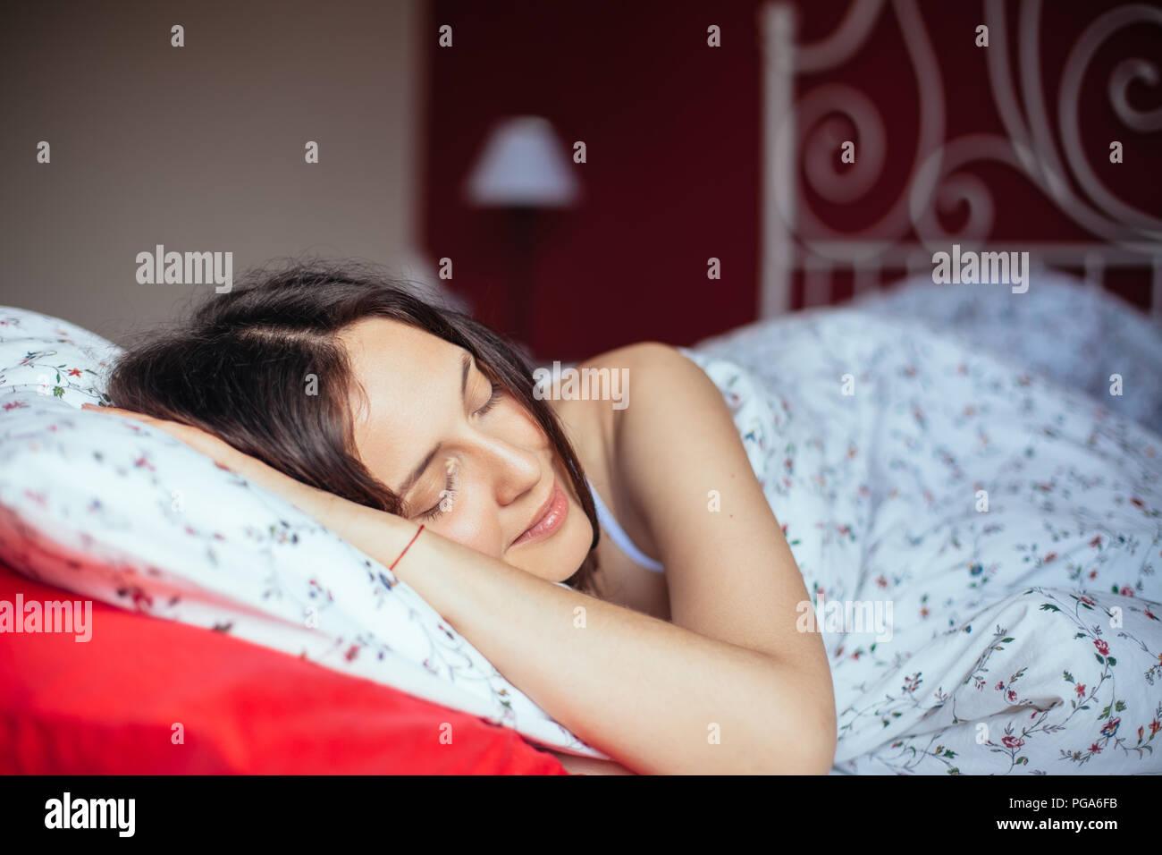 Giovane donna sorridente mentre dorme nel suo letto a casa. Concetto di relax Immagini Stock
