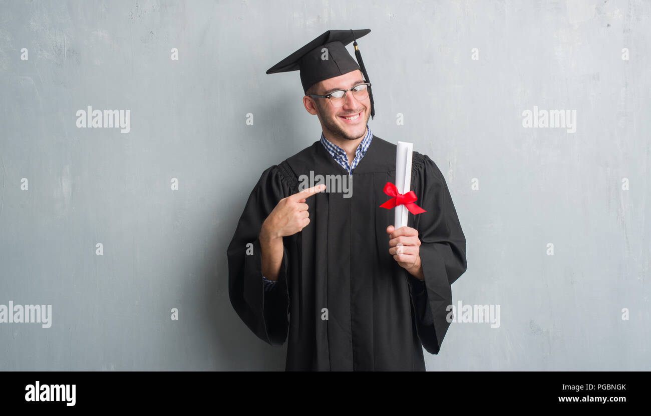 Giovane uomo caucasico su grigio parete grunge indossando graduate uniforme  grado di contenimento molto felice puntando 5cd9d9f8d20e