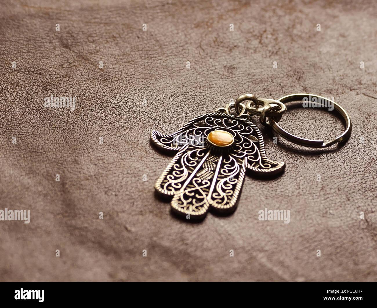 Un anello chiave nella forma di Fatima la mano sulla pelle marrone dello sfondo. Simbolo di antico e di moderno e tradizionale souvenir turistici della Tunisia. Immagini Stock