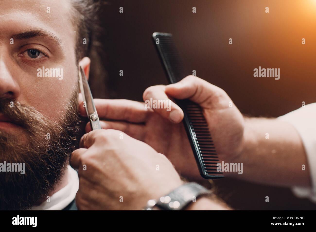 Barbiere con interni in legno. Modello barbuto uomo e barbiere. Foto Stock