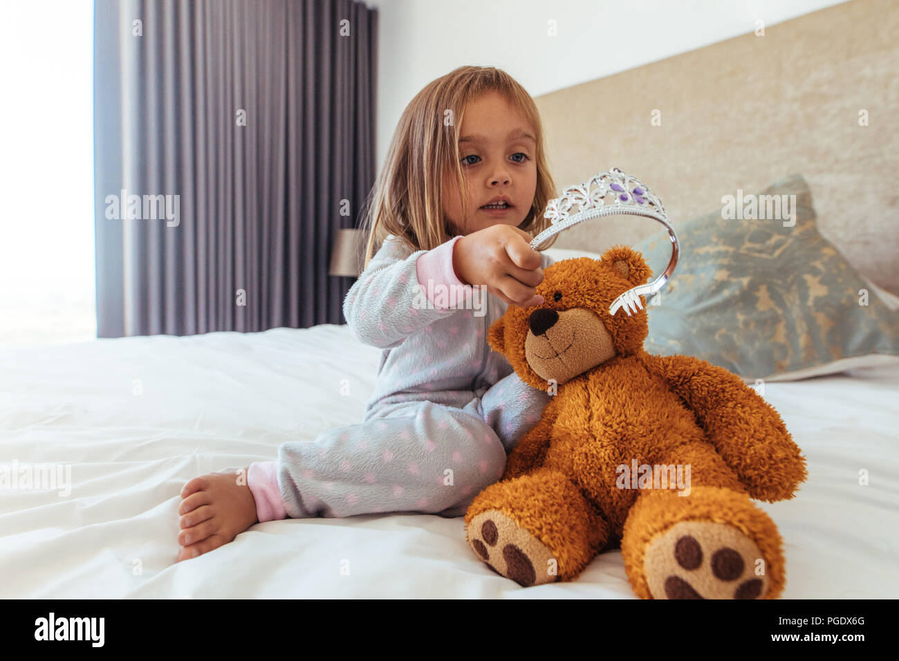 Giovane ragazza innocente mettendo una corona sul suo orsacchiotto di peluche. Bambina gioca con il suo giocattolo morbido. Immagini Stock