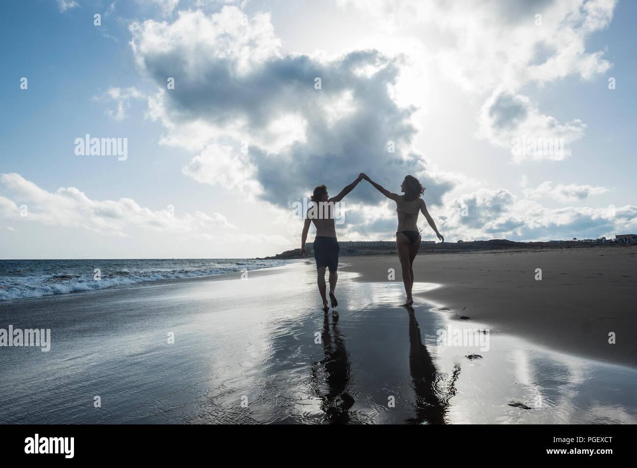 Di felicità e di gioia di concetto per la giovane coppia di bella gente visto dal retro camminando sulla riva di toccare le mani vicenda. Amore e amici Foto Stock
